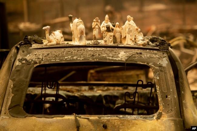 Figuras de un pesebre sobre un auto calcinado después del incendio Camp Fire, en Pearson Road, el lunes 12 de noviembre de 2018, en Paradise, California (Foto AP / Noah Berger)