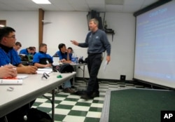 In this June 30, 2009 file photo, Larry Wostenberg teaches an engine management systems class at the WyoTech technical school, which was operated by Corinthian Colleges Inc, at their campus in Laramie, Wyoming