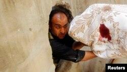 Ozod Suriya armiyasi jangchisi marhum safdoshini Halabdagi to'qnashuvdan olib chiqmoqda.