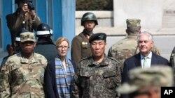 El secretario de Estado de EE.UU., Rex Tillerson (derecha) junto al vice comandante surcoreano de las fuerzas combinadas, general Leem Ho-young, (segundo desde la derecha), y dos soldados norcoreanos (izquierda arriba y al centro) miran hacia el Sur en el poblado fronterizo de Panmunjom, Corea del Sur, el viernes, 17 de marzo, de 2017.