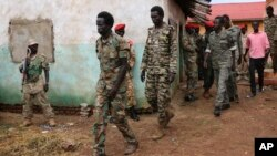 FILE - South Sudanese soldiers accused of a horrific attack on foreign aid workers including rape, torture, killing and looting on the Terrain hotel compound, are assisted to a prison van after attending their trial in Juba, South Sudan.