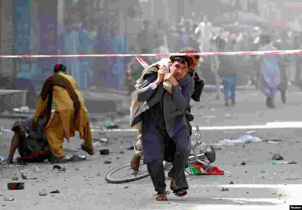 아프가니스탄 잘랄라바드에서 폭탄 테러 사건이 발생한 후 남성이 부상자를 업고 병원으로 뛰어 가고 있다. 폭발 사건은 영국으로부터 독립한 지 100주년을 맞이 되는 날로, 공휴일인 이 날 많은 시민들이 거리로 나와 있었다.