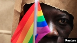 FILE - An asylum seeker from Uganda covers his face with a paper bag to protect his identity as he marches with the LGBT Asylum Support Task Force during the Gay Pride Parade in Boston, Massachusetts, June 8, 2013.