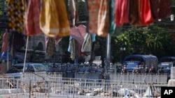 在国际妇女节这一天,在仰光街头,缅甸防暴警察列队站在路障前,抗议者高高张挂女性服装。(2021年3月8日)
