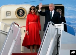 FILE - President Donald Trump waves from Air Force One with First Lady Melania and son Barron.