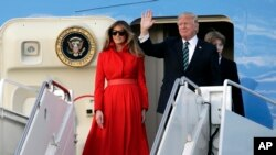 President Donald Trump waves from Air Force One with First Lady Melania and son Barron after arriving at Palm Beach International Airport, March 17, 2017, in West Palm Beach, Florida, to spend the weekend at his Mar-a-Lago Estate in Palm Beach.