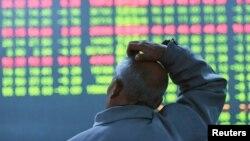 Nhà đầu tư nhìn vào màn hình thông tin chứng khoán tại một trung tâm môi giới ở Hàng Châu, tỉnh Chiết Giang, ngày 11/1/2016.