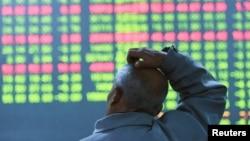 杭州一名男子站在股票市場看電子看板。