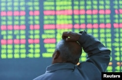 FILE - An investor looks at an electronic screen showing stock information at brokerage house in Hangzhou, Zhejiang Province, China, Jan. 11, 2016.