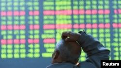 11일 중국 저장성 항저우 시 증권 거래소에서 한 투자가가 증권 현황을 나타낸 전광판을 주시하고 있다.