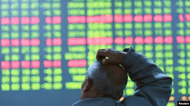 FILE - An investor looks at an electronic screen showing stock information at a brokerage house in Hangzhou, Zhejiang Province, China, Jan. 11, 2016.