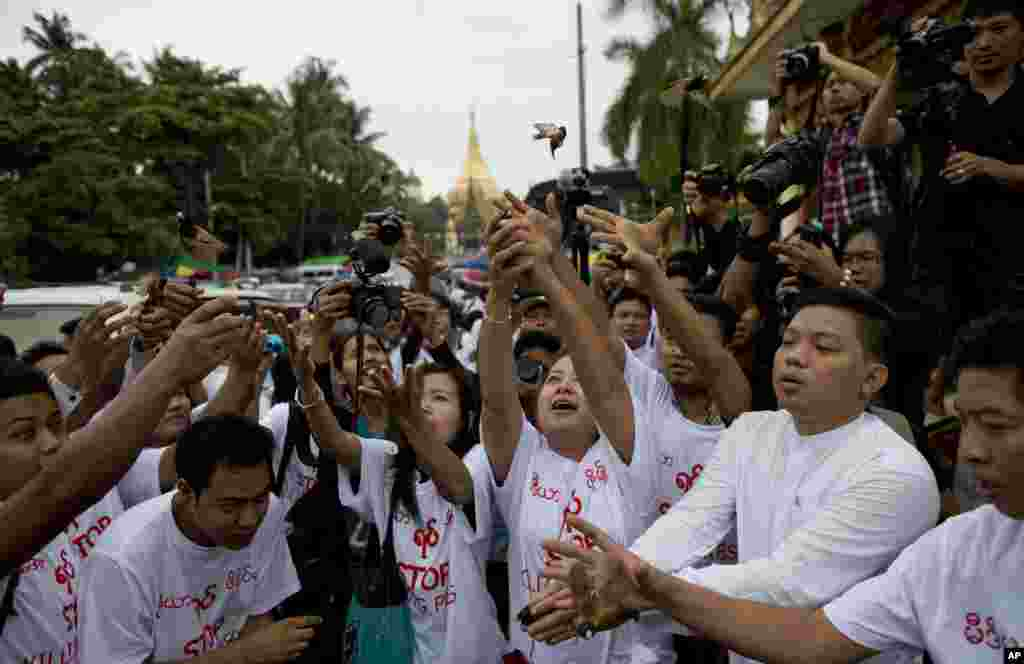 """Myanmar (also known as Burma) journalists release imprisoned birds after a prayer session in Yangon in support of four reporters and the chief executive of the Yangon-based """"Unity Journal."""" The journalists were sentenced Thursday to 10 years of hard prison labor for violating national security by writing and publishing stories about a weapons factory."""