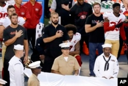 Kaepernick, at center, kneels during the national anthem before the NFL preseason football game against the San Diego Chargers, Sept. 1, 2016.