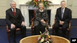 In this image released by Northern Ireland Government Assembly, showing US Secretary of State Hillary Rodham Clinton, centre, sitting with First Minister Peter Robinson, right, and deputy First Minister Martin McGuinness, as they pose together in Belfast