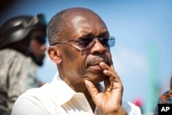 FILE -- Haiti's former President Jean-Bertrand Aristide looks on after speaking to supporters at a campaign event for presidential candidate Maryse Narcisse of the Fanmi Lavalas political party, in Port-au-Prince, Haiti.