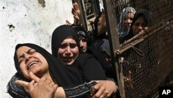 Palestinian relatives react during the funeral of a Islamic Jihad militant killed in an Israeli air strike, in Khan Younis, southern Gaza Strip, March 30, 2011