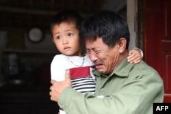 Ölənlərin arasında olduğu güman edilən 30 yaşlı Le Van Hanın atası Le Minh Tuan qucağında Hanın oğlunu tutub. Nghe An vilayəti, Vyetnam. 27 oktyabr, 2019.