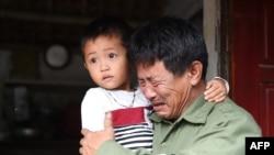 Ông Lê Minh Tuấn, cha của Lê Văn Hà, có thể là một trong số 39 người chết trong chiếc xe tải ở bên Anh,. Ông Tuấn ẵm cháu, con của ông Hà. Ảnh chụp ở Nghệ An hôm 27/10/2019.