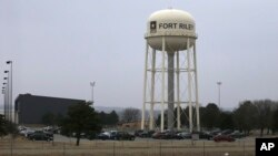 FILE - Vehicles park around a water tower at Fort Riley, Kan.