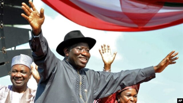 Nigerian President Goodluck Jonathan (C), accompanied by his wife Patience (R), Vice President Namadi Sambo, waves to the crowd before their campaign declaration in Abuja on September 18, 2010.