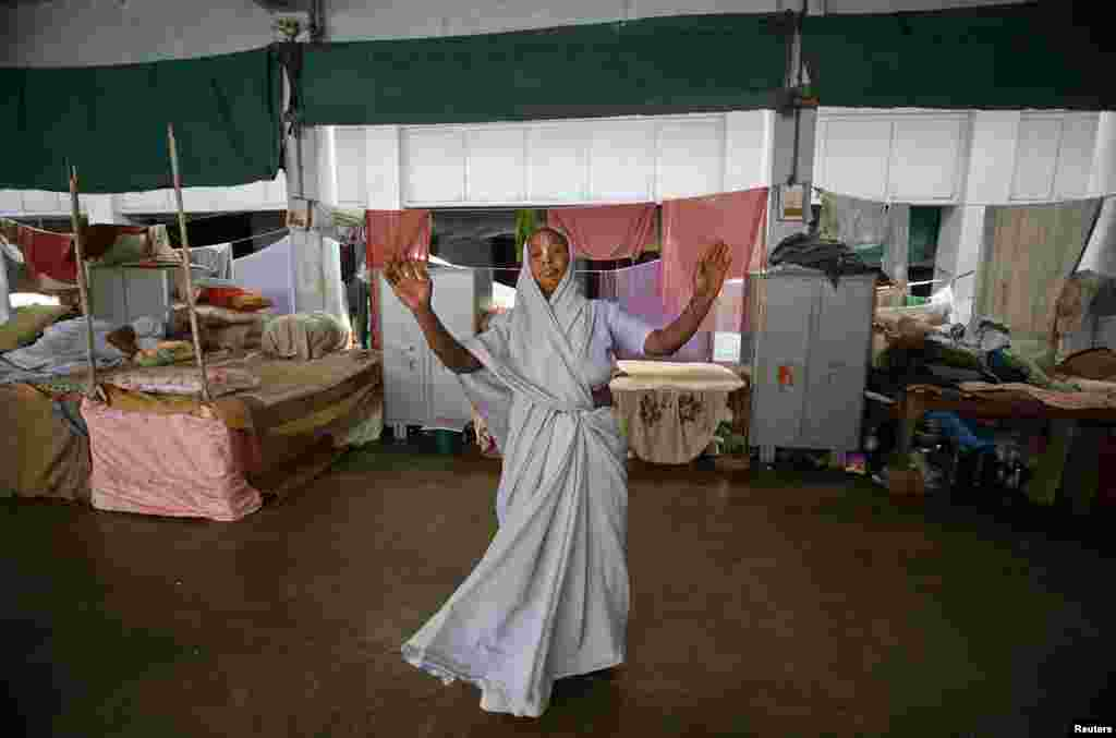 A widow dances in a dormitory during Holi celebrations at the Meera Sahavagini ashram in Vrindavan, Uttar Pradesh, March 24, 2013.