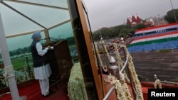 India's Prime Minister Manmohan Singh addresses the nation from a bullet-proof enclosure at the historic Red Fort during Independence Day celebrations in Delhi, August 15, 2013.