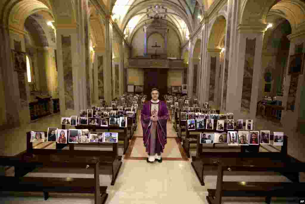 Robbiano Church parson, Don Giuseppe Corbari, poses next to selfies sent by his parishioners and pasted on the pews of the Robbiano church, as Masses for the faithful have been suspended following Italy's coronavirus emergency, in Giussano, northern Italy.