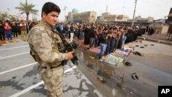 Một thành viên của lực lượng an ninh Iraq đứng canh các tín đồ tiến hành cầu nguyện ngoài trời hôm thứ Sáu tại Sadr City ở Baghdad, Iraq, ngày 30/10/2015.