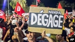 "A protester holds a banner reading ""Nahda go away"" during a demonstration against Tunisia's Islamist-led government, August 6, 2013 in Tunis."
