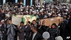 Mourners carry the coffins of two slain pilgrims killed in a bombing in the Shiite city of Najaf, 160 kilometers (100 miles) south of Baghdad, Iraq, February 13, 2011.