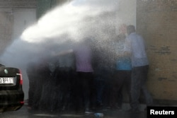 FILE - Turkish riot police use water cannon to disperse Kurdish demonstrators protesting against the removal of the local mayor from office over suspected links with Kurdish militants, in Diyarbakir, Turkey, Sept. 11, 2016.