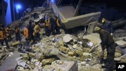 Rescuers search for survivors in the rubble of a collapsed hotel in Van, eastern Turkey, late Wednesday, Nov. 9, 2011.