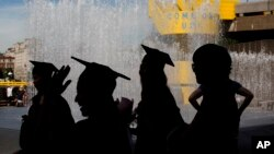 Students wearing their graduation gowns and caps are silhouetted as they stand beside a fountain on the southbank of the River Thames in London.