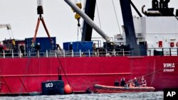 The turret of sunken privately built and owned submarine submarine UC3 Nautilus is seen by the side of a salvage vessel during an operation taking place in connection with a criminal investigation, in Oeresund strait near Copenhagen, Denmark, Saturday, Aug. 12, 2017. Danish prosecutors urged a judge on Saturday to hold in pre-trial detention the owner of an amateur-built submarine, suspected of being responsible for the disappearance of a Swedish woman who had been onboard the ship that later sank.