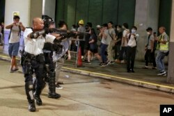 2019年7月30日一名香港警察舉槍瞄準了在香港葵涌警署大樓前聲援被拘捕的反送中抗議者的示威人群。