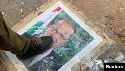 Një demostrues shkel mbi portretin e presidentit Michel Aoun,