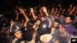 伊拉克防爆警察5月21日阻止抗议者冲入巴格达东南部340公里的巴士拉省政府大楼。