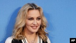 """FILE - Madonna poses for photographers upon arrival at the World premiere of the film """"The Beatles, Eight Days a Week"""" in London."""