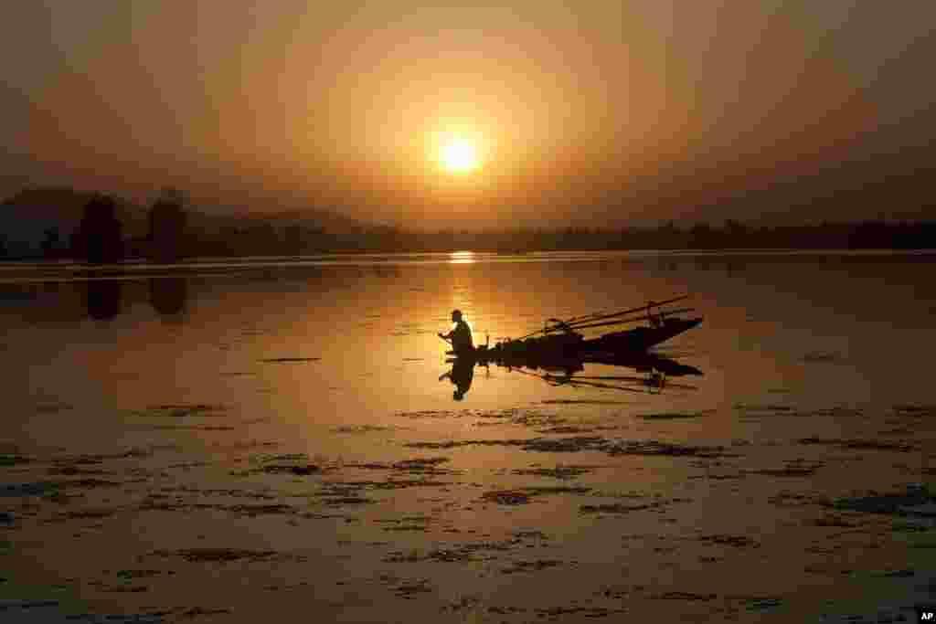 Um pescador Kashmiri rema a sua Shikara, um barco tradicional, em pleno pôr do sol no Lago Dal em Srinagar, Índia.