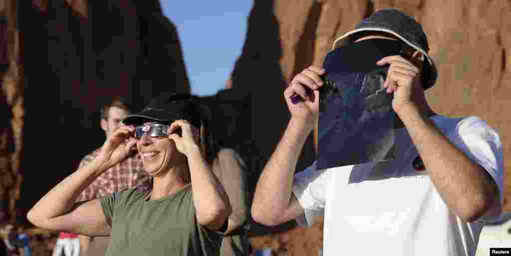 Tourists look through solar eclipse glasses and solar viewers during an annular eclipse in Monument Valley Tribal Park in Utah.