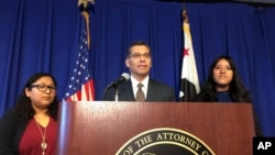 California Attorney General Xavier Becerra is flanked by Rosa Barrientos, of East Los Angeles, left, and Eva Jimenez, of Visalia, right, as he announces a lawsuit challenging the Trump administration's decision to end a program that shields young immigrants from deportation.