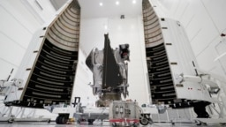 This Wednesday, Sept. 29, 2021 file photo shows NASA's Lucy spacecraft with its housing at the AstroTech facility in Titusville, Fla. It will be first space mission to explore a diverse population of small bodies known as the Jupiter Trojan asteroids. (AP Photo/John Raoux, File)