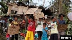Trẻ em Philippines cầm bảng kêu gọi sự giúp đỡ dọc theo con đường cao tốc tại thị trấn Tabogon trong tỉnh Cebu, miền Trung Philippines, ngày 11/11/2013.