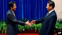 中国国家主席习近平和日本首相安倍晋三在人民大会堂握手。(2014年11月10日)