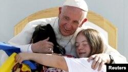 El papa Francisco abraza a dos jóvenes con síndrome Down en el estadio José María Pavón de Morelia.