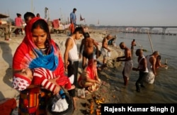 A Hindu woman carries her child as she performs rituals on Ashtami, the eighth day of Navratri festival at Sangam. This is where the Ganges and Yamuna rivers meet in Prayagraj, India, April 1, 2020.