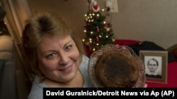 In this Dec. 9, 2019, photo Julie Ruttinger holds a 141-year-old fruitcake baked by her great-great-grandmother, Fidelia Ford. (David Guralnick/Detroit News via AP)