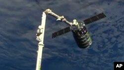 美国航天航空管理局提供的这张照片显示9月29日飞船与国际太空站机械臂相接
