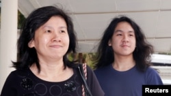 Teen blogger Amos Yee arrives with his mother at the State Courts in Singapore, Sept. 28, 2016.