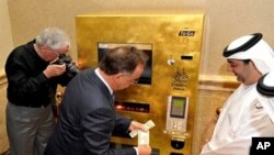 "Thomas Geissler (C), the chief executive of TG-Gold-Super-Markt, tries the ""Gold to Go"" vending machine at the Emirates Palace Hotel in Abu Dhabi, 12 May 2010."